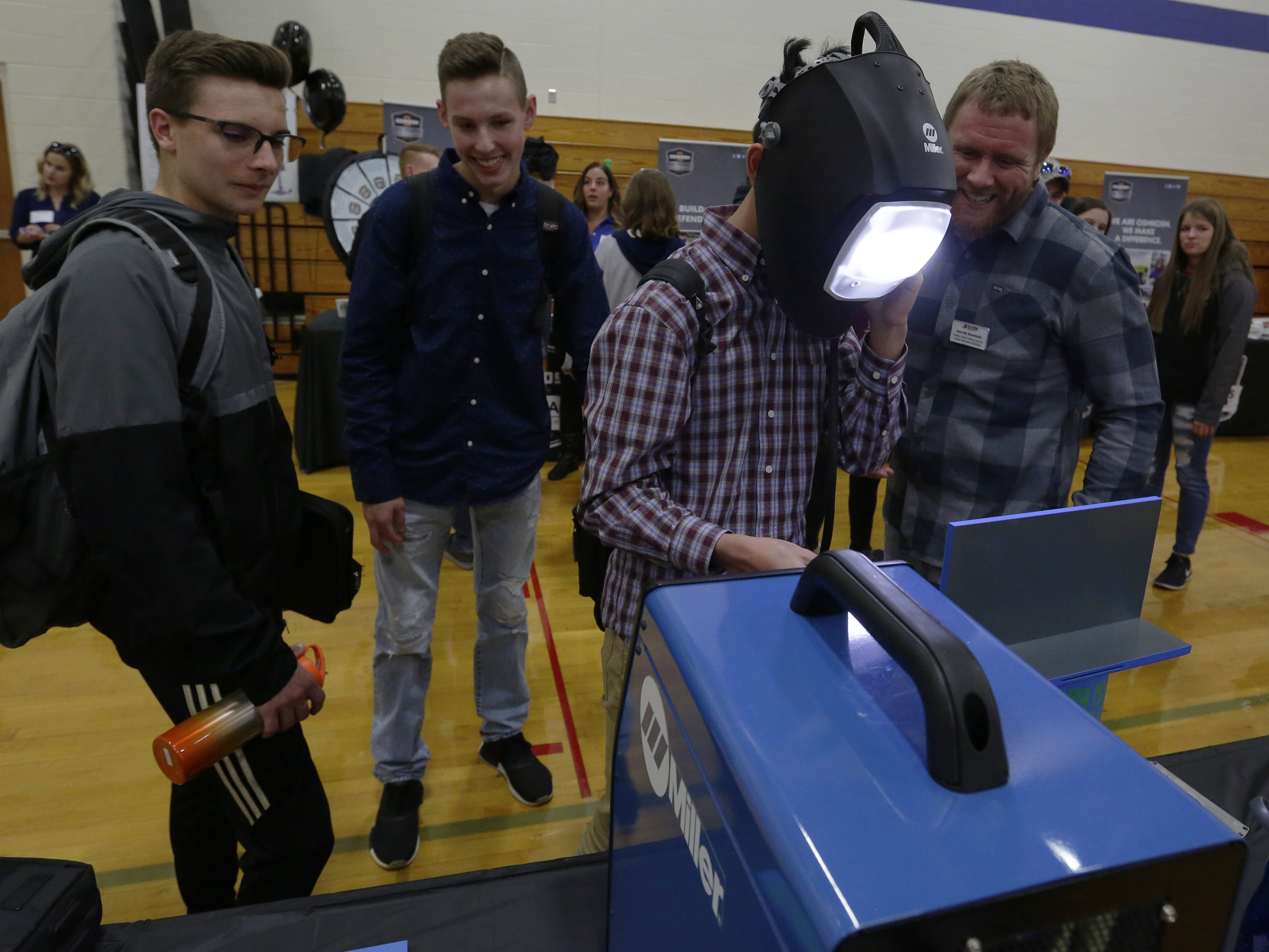 Garrett Kaminski of Fox Valley Technical College looks over the computerized welding that Max Jin is doing as his friends Nick Vey and John Rowe watch Tuesday, Oct. 23, 2018, during the Oshkosh Chamber of Commerce's Career Exploration Fair at Oshkosh West High School. About 1,000 students from Oshkosh and Omro middle and high schools participated in this year's expanded fair, thanks to a $5,000 grant from AT&T.