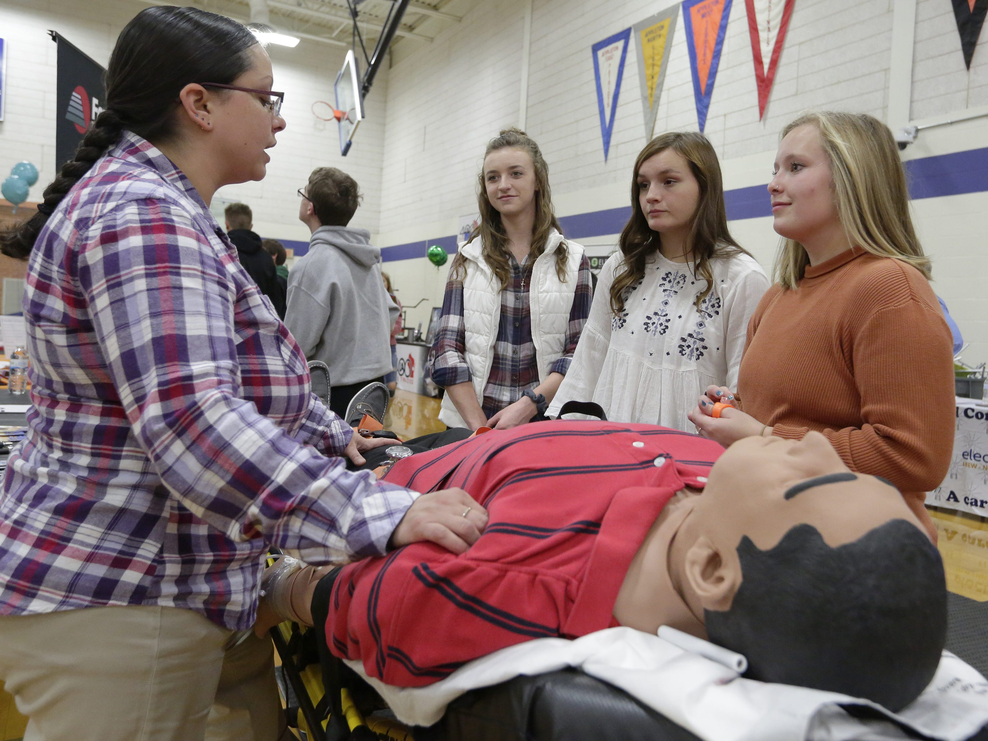 Jillian Camara Foss of Fox Valley Technical College talks to Danycka Millis, Sydney La Croix and Hanna Kramer about being a paramedic Tuesday, Oct. 23, 2018, during the Oshkosh Chamber of Commerce's Career Exploration Fair at Oshkosh West High School. About 1,000 students from Oshkosh and Omro middle and high schools participated in this year's expanded fair, thanks to a $5,000 grant from AT&T.
