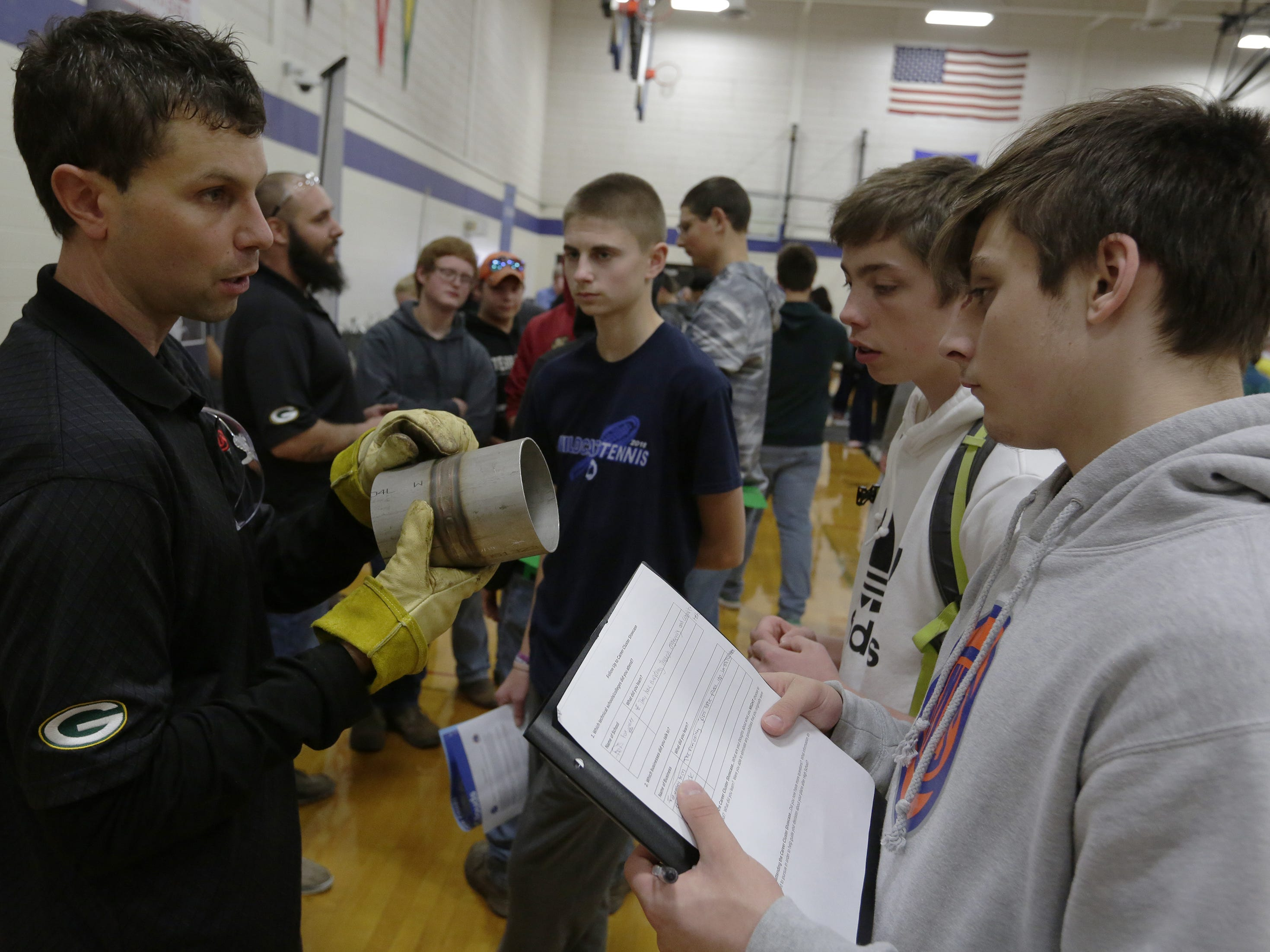 D.J. Kloida, youth apprenticeship coordinator with UA 400 Pipe Trades, talks with Ian Steward and Matt Hientzelmeier during the Oshkosh Chamber of Commerce's Career Exploration Fair on Tuesday, Oct. 23, 2018, at Oshkosh West High School. About 1,000 students from Oshkosh and Omro middle and high schools participated in this year's expanded fair, thanks to a $5,000 grant from AT&T.