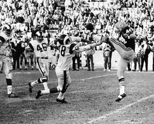 Linebacker Tony Gullory (88) of the Los Angeles Rams blocks a punt by Danny Anderson of the Green Bay Packers in the final minute of their game in Los Angeles, on Dec. 9, 1967. Claude Crabb of the Rams (not shown) picked up the ball and ran it to the five-yard line, from where the Rams scored two plays later to win 27-24 and keep their hopes alive for the championship of the Coastal Division of the National League.