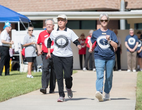 From left, Billy McLean, of Westminster Village in Spanish Fort, Alabama; Barbara Price, of Magnolia Trace in Huntsville, Alabama; and Gail Childs, of Azalea Trace in Pensacola, race the first leg of the walking relay Wednesday during the OlympiActs competition.