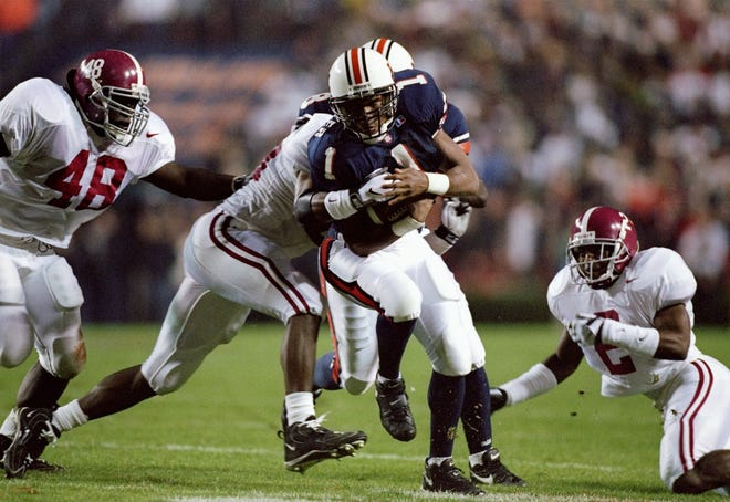 22 Nov 1997:  Demontray Carter of the Auburn Tigers tries to carry the ball past cornerback Deshea Townsend (right) and Trevis Smith of the Alabama Crimson Tide during a game at the Jordan-Hare Stadium in Auburn, Alabama.  Auburn won the game 18-17. Manda