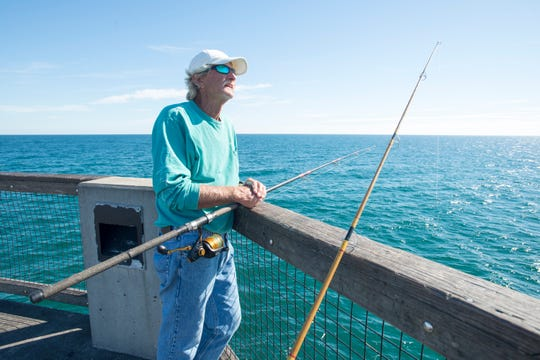 Rodney Pate fishes off the Navarre Beach Fishing Pier on Wednesday, October 24, 2018.