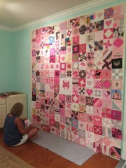 A group of women work on the Pink Ribbon Project quilt organized by Virginia Moody.
