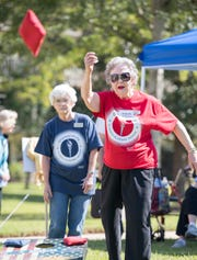 At left, Betty Ann Lurton, of Pensacola's Azalea Trace, looks on as Rochelle Robinson, of Westminster Village in Spanish Fort, Alabama, tosses a bean bag Wednesday during the cornhole event at the OlympiActs competition.