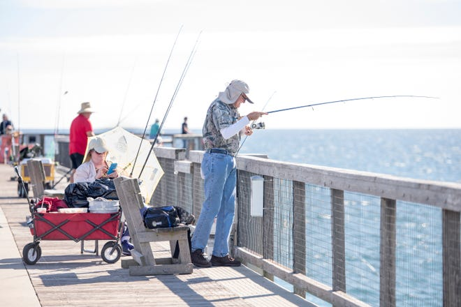 Terry Browning, right, of Lawton, Oklahoma, fishes off the Navarre Beach Fishing Pier on Wednesday, October 24, 2018.