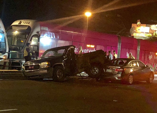 A pickup truck came to rest on the back end of a sedan after colliding with a light-rail train in Phoenix on Tuesday night.