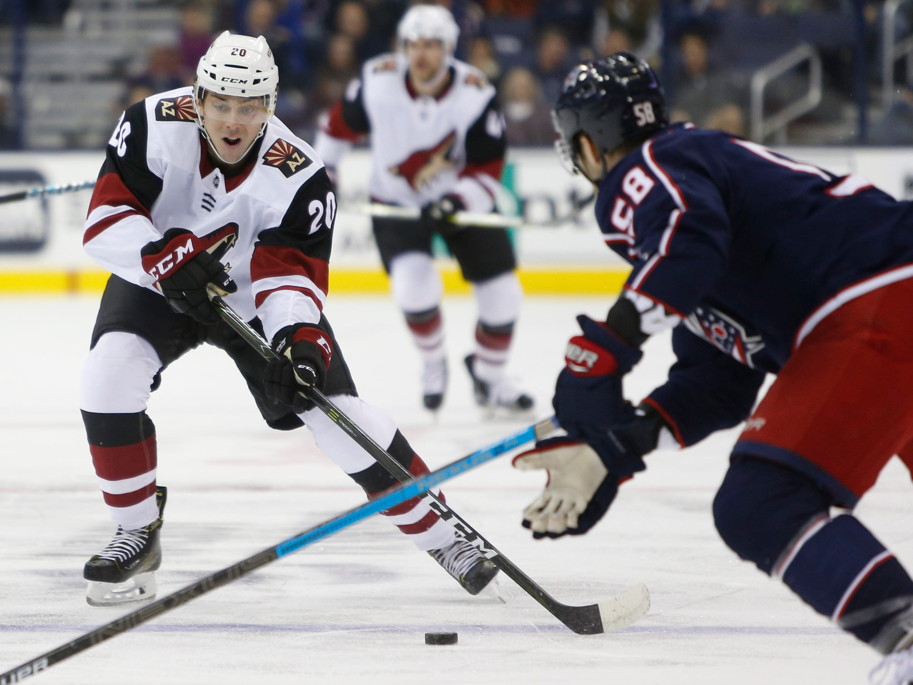 Arizona Coyotes' Dylan Strome, left, carries the puck across the blue line as Columbus Blue Jackets' David Savard defends during the first period of an NHL hockey game Tuesday, Oct. 23, 2018, in Columbus, Ohio.