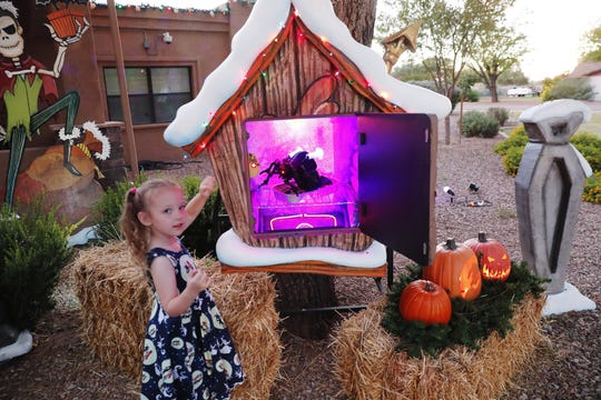 Samantha Brown, 5, plays with a display at her home in Tempe, Ariz. October 23, 2018. Jessica and Francis Brown host an elaborate and professionally done Halloween/Christmas display.