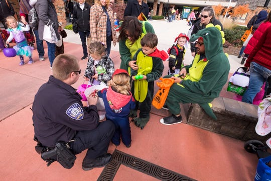 St. Clair Police Officer Colin Ellul offers candy to kids dressed in different costumes Wednesday, Oct. 24, 2018 during  the Party for Tots, the first event in the city's Halloweekend.