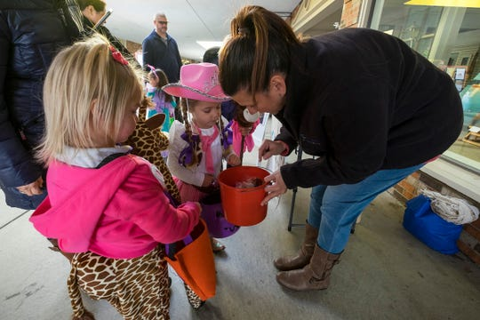Heather Hayes, right, hands out candy to Olivia Goldfarb, 4, center and Alaina Sinclair, 4, Wednesday, Oct. 24, 2018 during  the Party for Tots, the first event in the city's Halloweekend.