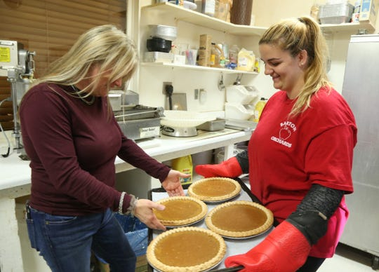From left,  Barton Orchards farm stand and bakery store manager Jill Stanton and head baker Cindy Murray look over a batch of pumpkin pies on October 24, 2018.