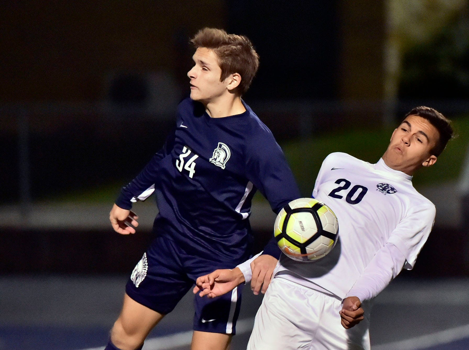 Chambersburg's Garrick Hill (34) heads the ball in front of Gabe Wunderlich (20) of Dallastown. Chambersburg lost a first round D3 soccer match to Dallastown 2-1 on Tuesday, Oct. 23, 2018.
