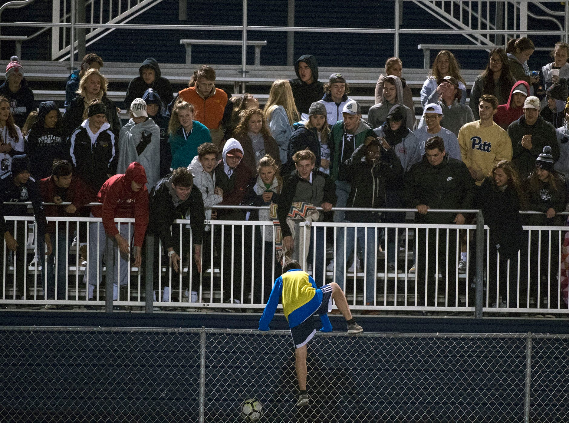 Chambersburg fans watch as a ball boy climbs the fence to chase a ball. Chambersburg lost a first round D3 soccer match to Dallastown 2-1 on Tuesday, Oct. 23, 2018.