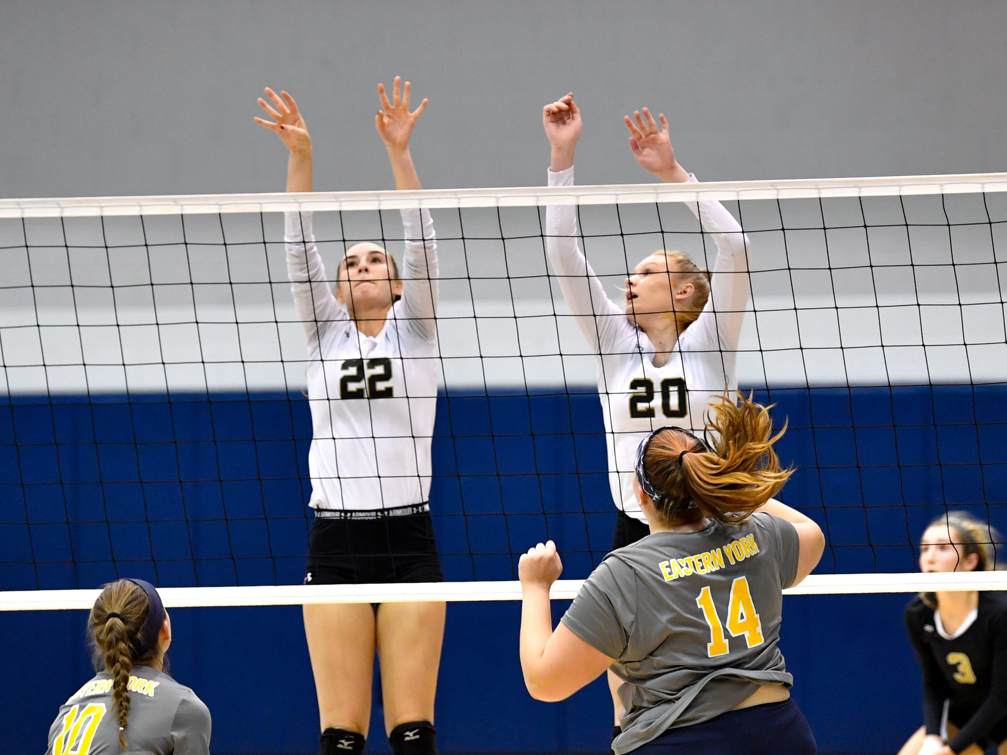 Delone Catholic's Emily Miller (22) and Brooke Lawyer (20) deflect the ball during the YAIAA league volleyball tournament semifinals between Eastern York and Delone Catholic, Tuesday, October 23, 2018. The Squirettes defeated the Golden Knights 3-2.