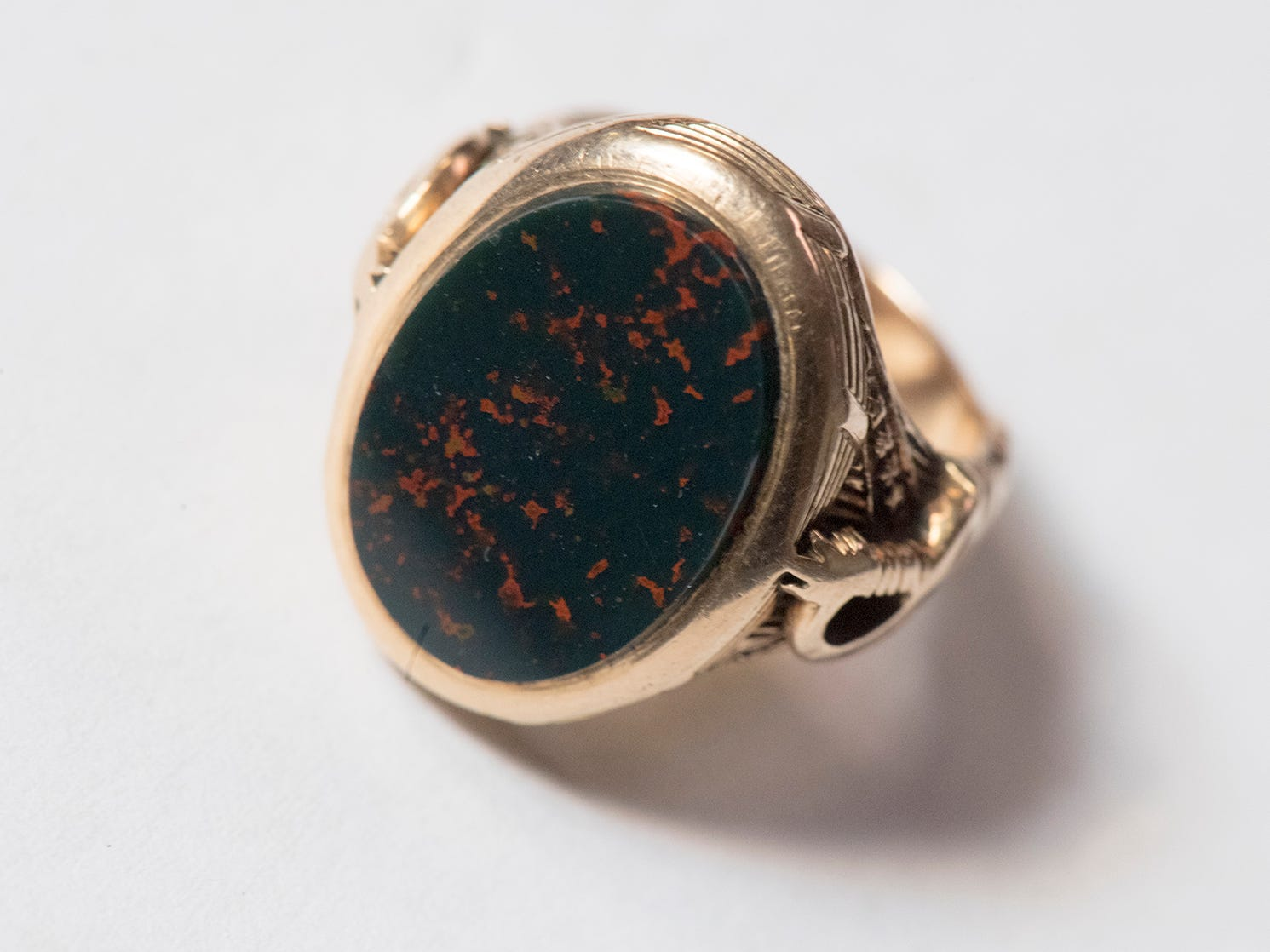 "This is a U.S. Military Academy gold ring featuring a flat green polished stone with red inclusions. The ring has an inscription of the ""Frank P Blair, Class of 77, USMA"""