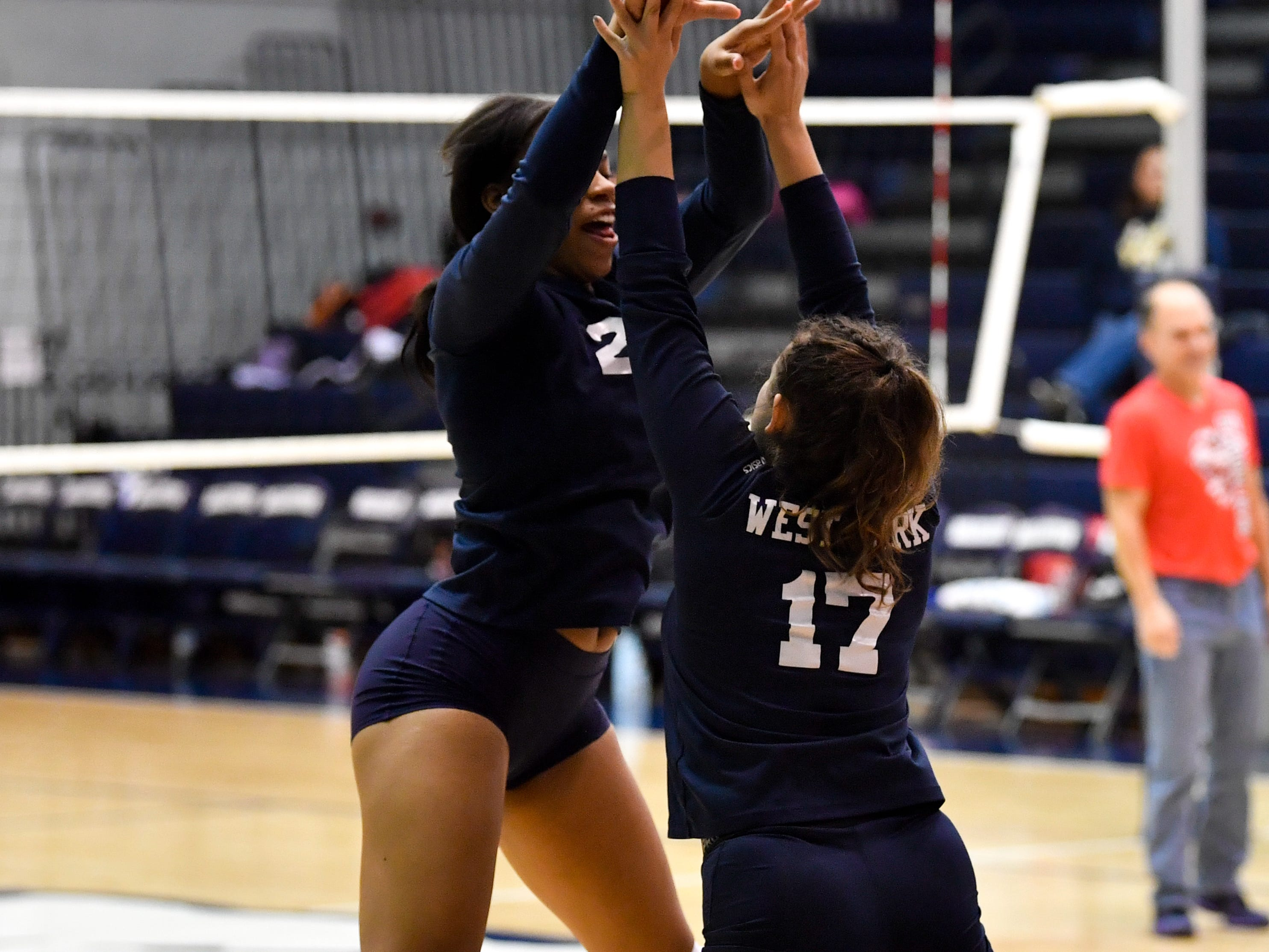 Alayna Harris (23) and Taylor Morley (17) give each other a high-five during the YAIAA league volleyball tournament semifinals between West York and Dover, Tuesday, October 23, 2018. The Bulldogs defeated the Eagles 3-1.