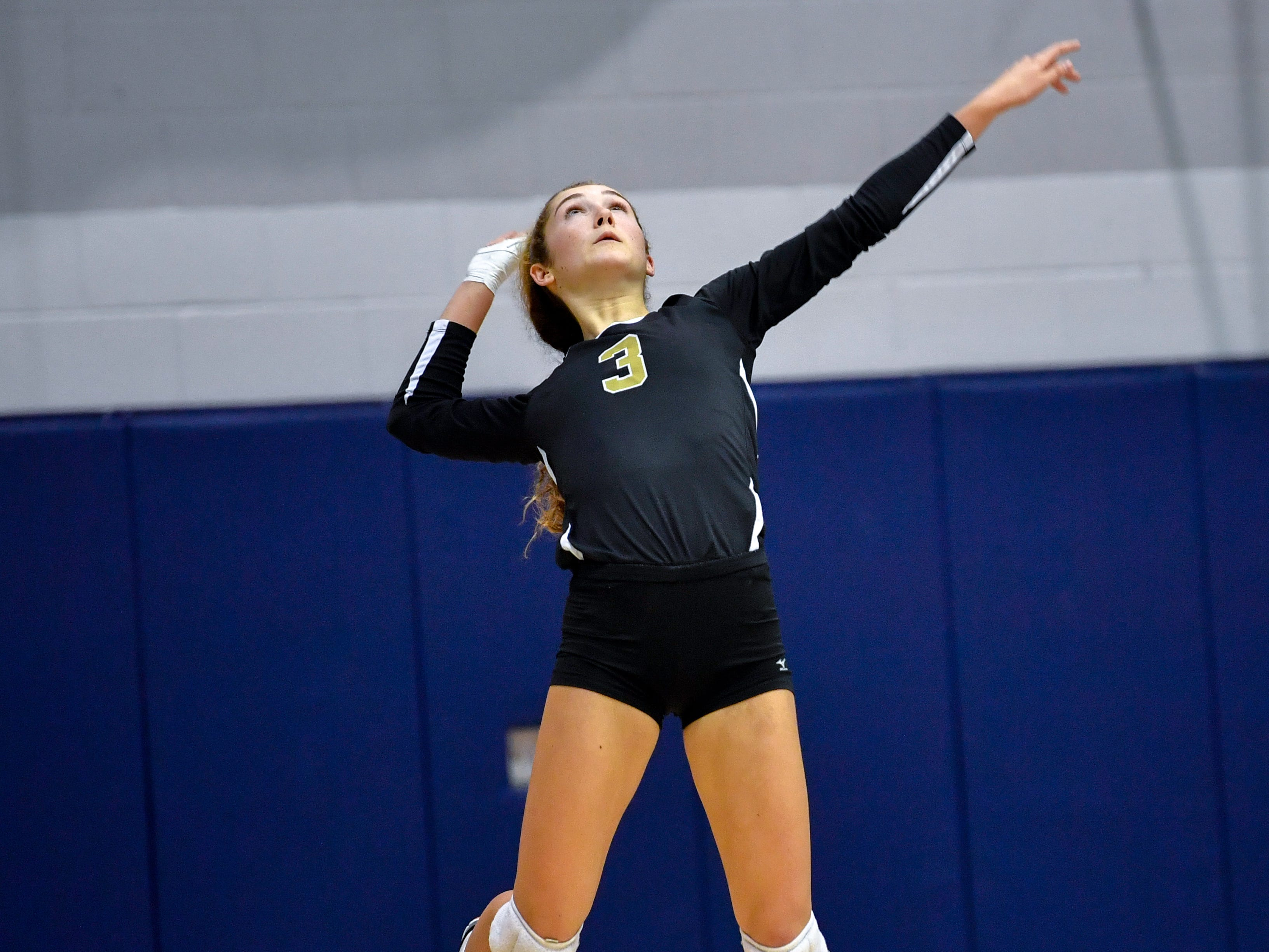 Lauren Trummer (3) of Delone Catholic performs a jump serve during the YAIAA league volleyball tournament semifinals between Eastern York and Delone Catholic, Tuesday, October 23, 2018. The Squirettes defeated the Golden Knights 3-2.