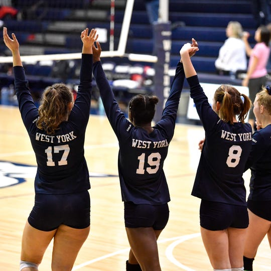 West York takes the court hand in hand during the YAIAA league volleyball tournament semifinals between West York and Dover, Tuesday, October 23, 2018. The Bulldogs defeated the Eagles 3-1.