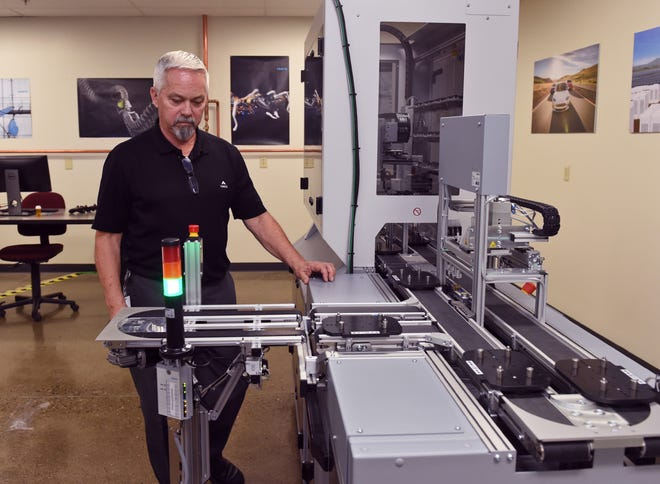 Randy Walden, advanced manufacturing instructor at Truckee Meadows Community College in Reno, stands next to an automated manufacturing machine at the TMCC Advanced Manufacturing Lab on Oct. 24, 3018.