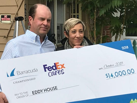 Chris Hoff, left, executive director of The Barracuda Championship, presents a check for $14,000 to Michelle Gehr, director of The Eddy House in Reno, on Wednesday.