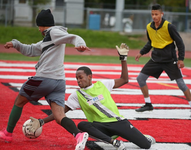 Edison's Esam Saleh, left, slips the ball past goalie Sumani Hassani, as defender Rey Arizmendi moves in to clear the ball during their team's practice on the turf at Franklin High School in Rochester Wednesday, Oct. 24, 2018.
