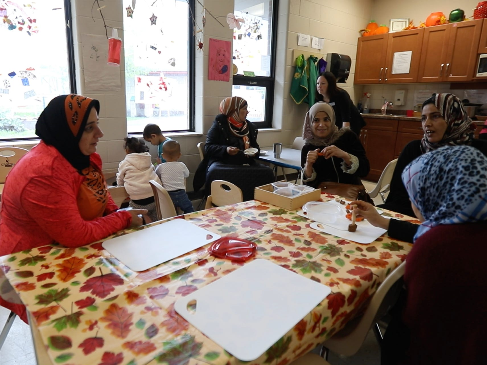 A group of mothers sit around a children's table playing with dough chatting while their children wander back and forth from the table. Ontario, Canada's Ministry of Education believes in promoting early learning and literacy.