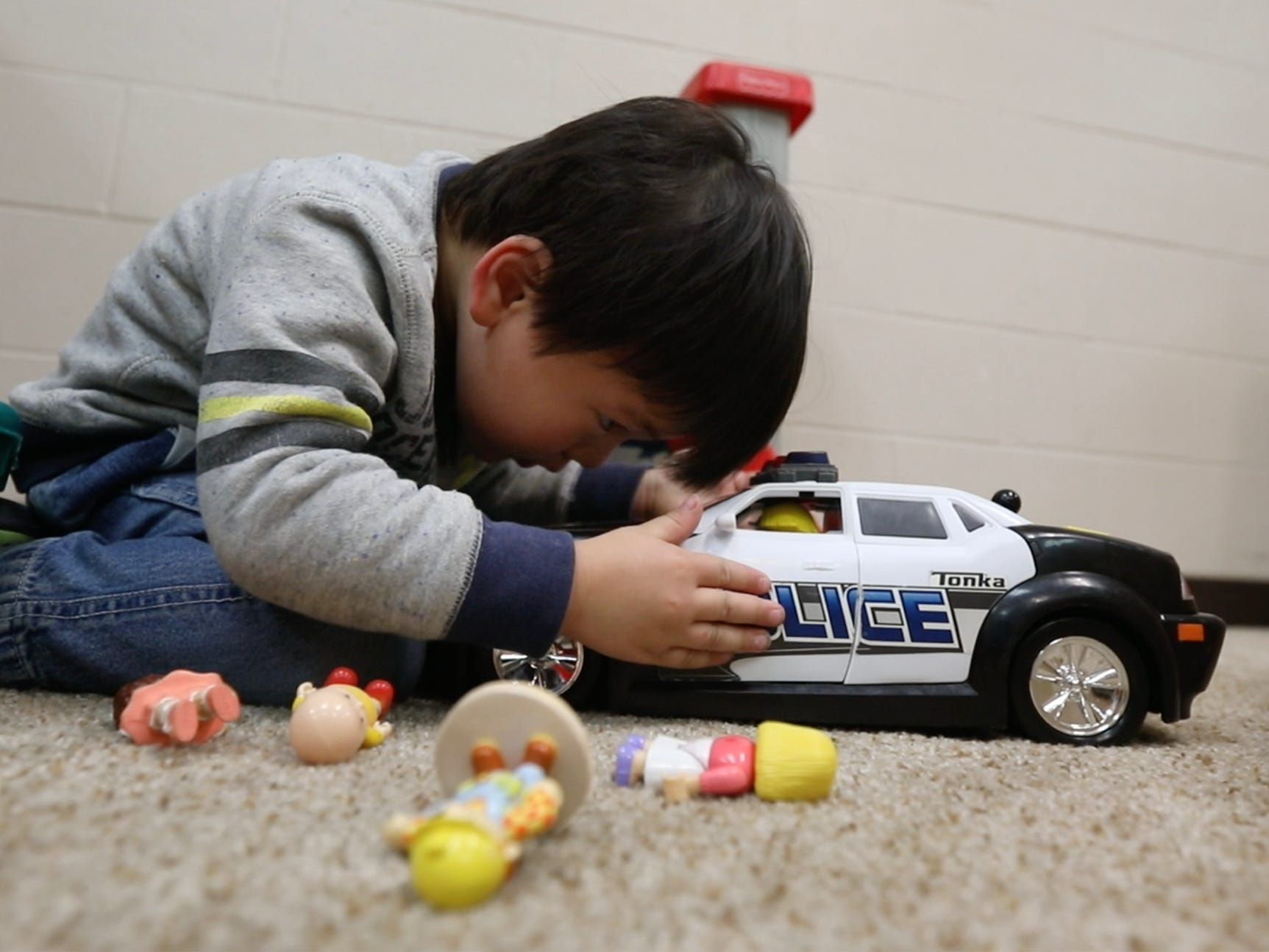 Yahoo He Zao looks in on the Little People he put in the police car he was playing with at Glengarry EarlyON Child and Family Centre.  Ontario Province funds these age 0 to 6 programs where parents and children can drop in and stay and play, which helps with child development.