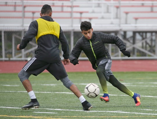 Edison's Mahbrook Saleh, right, moves hard towards the goal as he tries to get around teammate Rey Arizmendi for a shot on goal during their team's practice on the turf at Franklin High School in Rochester Wednesday, Oct. 24, 2018.