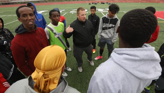 Edison coach A.J. Maio, center, goes over plans for drills and during their team's practice on the turf at Franklin High School in Rochester on Wednesday, Oct. 24, 2018.