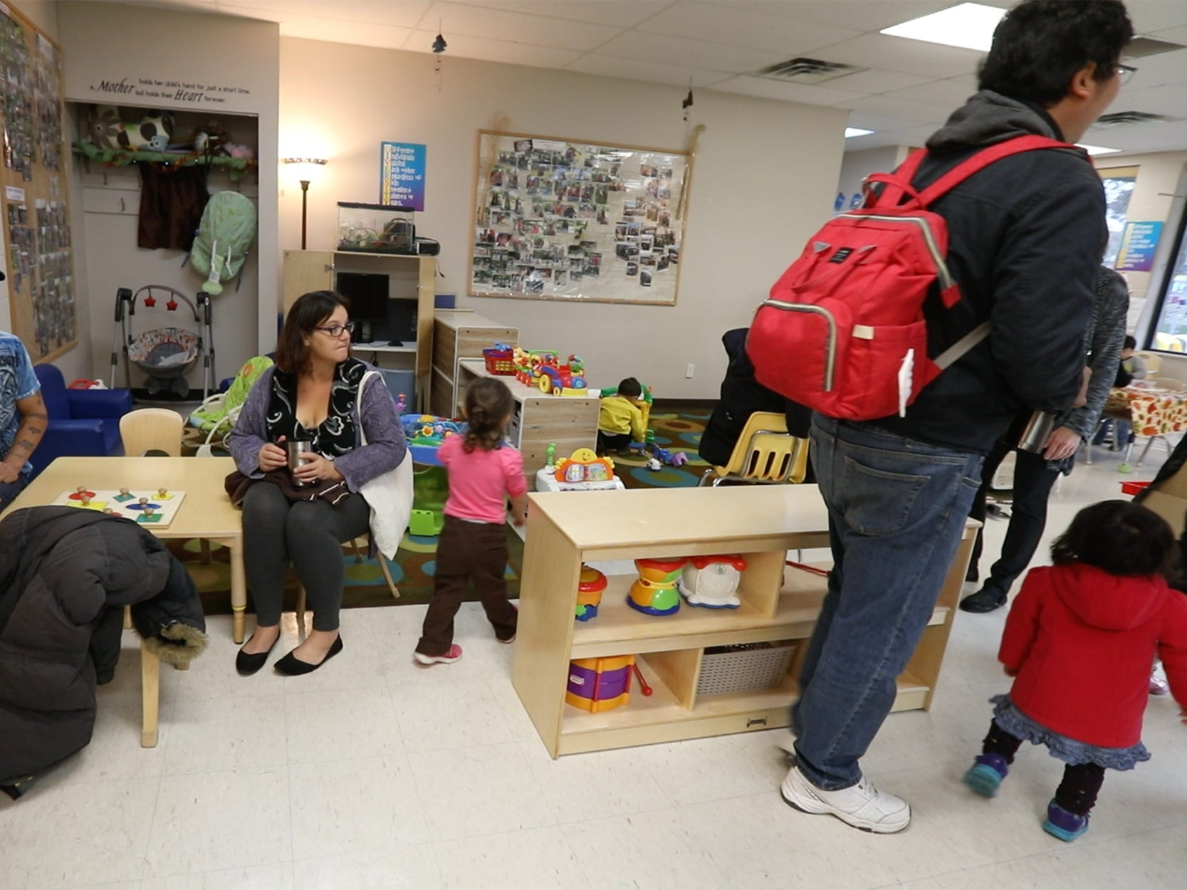 Mark and Florence Carter watch as several children congregate near the painting area as their daughter, Renay, 2, wanders towards another play area.  The program is not income based it is open to all people.