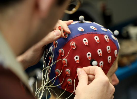 David Richardson, a medical student and doctoral candidate at the University of Rochester Medical Center, fits electrodes into a cap on  Democrat and Chronicle reporter Patti Singer. The electrodes would record brain function as Singer walked on a treadmill and identified the direction of images on a screen. The Cognitive Neurophysiology Lab in the Del Monte Institute for Neuroscience is one of few labs with mobile brain/body imaging, which researchers are using to determine a relationship between cognition and mobility of people with Alzheimer's.