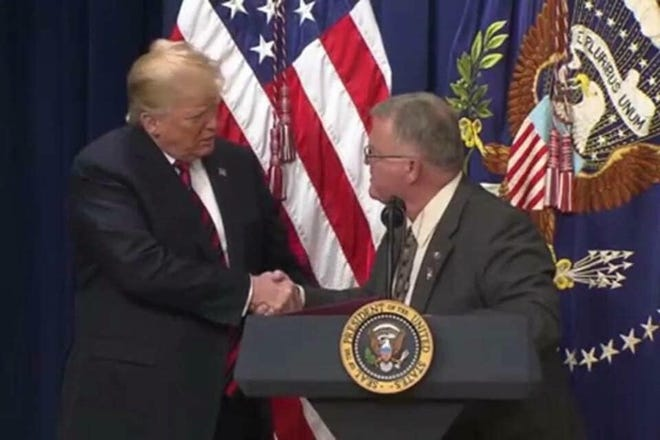 President Donald Trump shakes hands with Les Baugh, Chairman of the Shasta County Board of Supervisors.