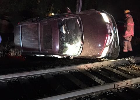 A single vehicle flips over near railroad tracks Tuesday after running a stop sign in Woodburn.