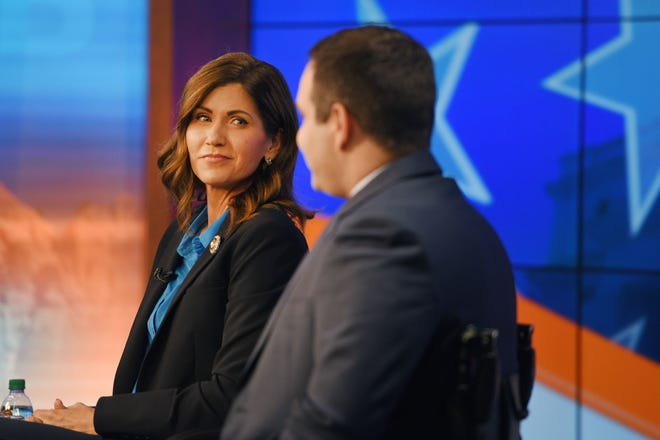 Kristi Noem listens to Billie Sutton during the gubernatorial debate Tuesday, Oct. 23, at KELO TV in Sioux Falls.