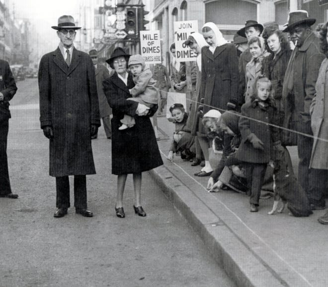 "February 1945 photo of Mayor William A. Grubert providing city support at the ""Mile of Dimes"" event, in which children lined up dimes along Beverley Street to help support the fight against infantile paralysis. Pictured to Grubert's left is Marion Smith, holding her nephew, Jerry Spencer Van Fossen."