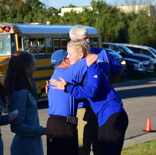 Fort Defiance's Sarah Moffett hugs her coach, Dave Stewart, after receiving her medal for her sixth-place finish in the girls varsity race at the Valley District Cross Country Championships on Tuesday, Oct. 23, 2018, at Mill Place Park in Verona, Va.