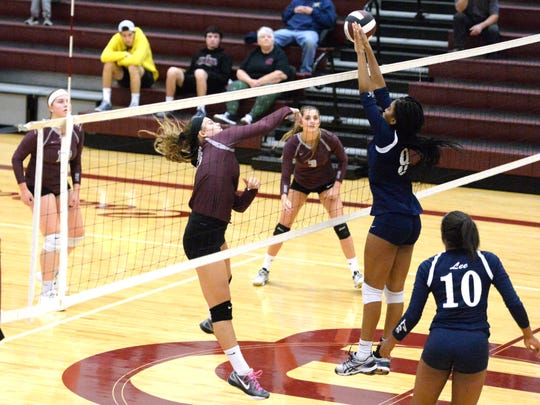 Lee High's Csayjah Whitelow (9) goes up to block a shot by Stuarts Draft's Madie Varner Tuesday night in the opening round of the Shenandoah District volleyball tournament. Lee won 3-1.