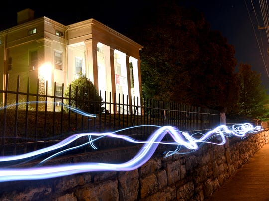 Streaks of light created through a timed camera exposure and a technique called light painting create streaks of light along the sidewalk out front of Stuart Hall School in Staunton on Tuesday, Oct. 23, 2018.