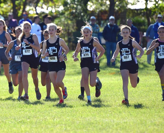 Fort Defiance's girls cross country team moves away from the starting line of its race at the Valley District Cross Country Championships on Tuesday, Oct. 23, 2018, at Mill Place Park in Verona, Va.