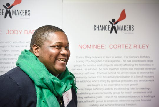 Cortez Riley poses for a photograph next to his nomination information on display Tuesday, Oct. 23, during the ChangeMakers awards ceremony at the St. Cloud Federal Credit Union.