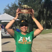 FAMU cross country head coach Darlene Moore raises the trophy after the men won the Mountain Dew Invitational on Saturday, Sept. 22, 2019 at the University of Florida.