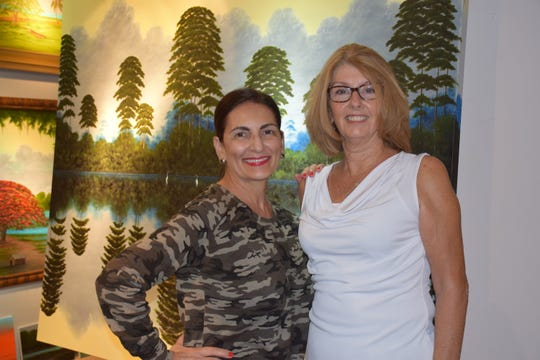 Vassie Malinos, left, and Kathy Jones at the Florida Highwaymen Landscape Art Gallery in downtown Vero Beach during the October First Friday Gallery Stroll.