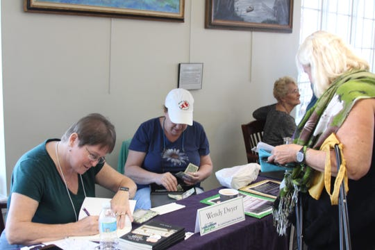 Local author Wendy Dwyer autographs a book for a woman at last year's event.