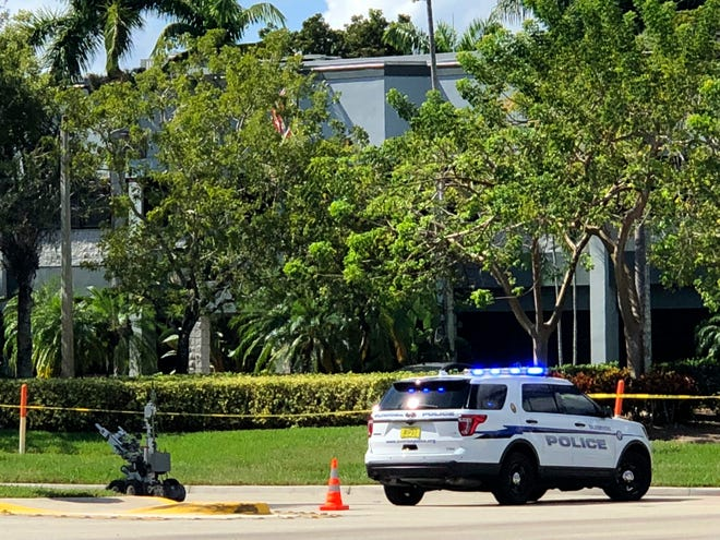 A Broward County Sheriff's Office bomb-defusing robot is deployed outside the office of U.S. Rep. Deborah Wasserman Schultz, where a suspicious package was discovered Wednesday, Oct. 24, 2018, in Sunrise, Fla.