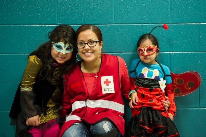 Red Cross volunteer Lilliana Matos celebrates Halloween with Fernanda and Maria Velasco.