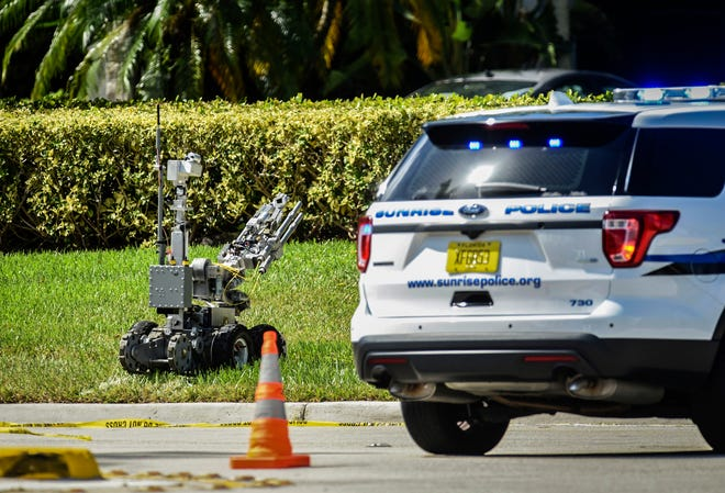 A Broward County Sheriff's Office bomb defusing robot is sent into the Sunrise Utility Administrative Center in Sunrise, Fla., Wednesday, Oct. 24, 2018, after a suspicious package was discovered in the building where Congresswoman Deborah Wasserman Schultz's office is located.