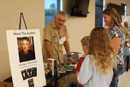 Local author George A. Bernstein talks about his books with library visitors.