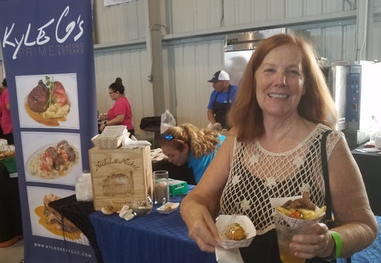 Big Taste of Martin County attendee Ruth Martini samples Kyle G's crab cake appetizer and steak frites entree.