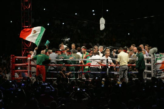 Julio César Chávez Jr., of Mexico, stands at the center of the crowded ring after his victory over Andy Lee, of Ireland, on Saturday night at the Sun Bowl. Chávez retained his WBC middleweight title.